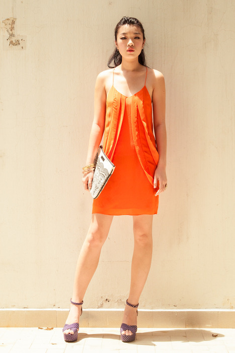 Aijek Swirl in Circles Tangerine silk dress matched with a DEBB clutch and Edge of Ember's assorted rings and bangles.