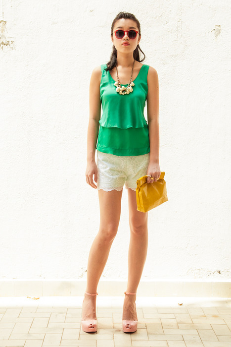 Aijek Little Secrets Tie back Top in emerald green matched with a lacey Pantone shorts. Matched with Marie Turnor Mustard Picnic clutch; chunky necklace and a pair of Quay shades.