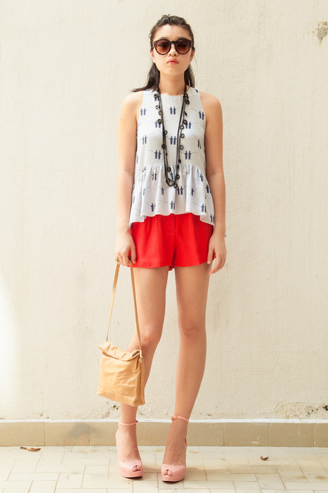 Aijek peplum top with paper bag shorts in coral, with Marie Turnor Picnic-on-the-go and Quay eyewear.